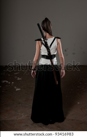Beautiful woman with her back towards the camera and katana on her back