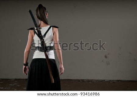 Beautiful woman with her back towards the camera and katana on her back - stock photo