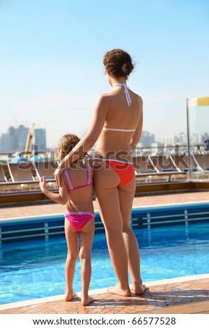 beautiful woman with her daughter standing near swimming pool. - stock photo