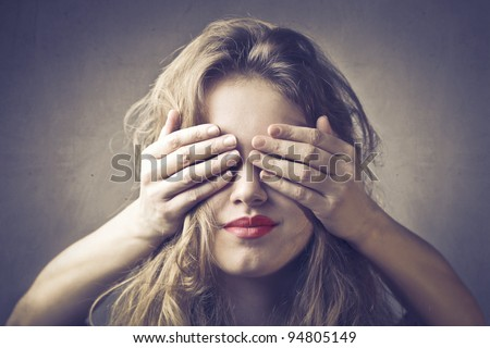 Beautiful woman with her eyes covered by someone else's hands - stock photo