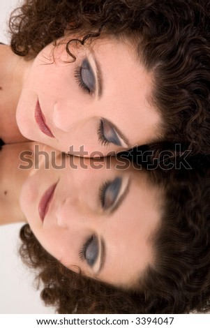 Beautiful woman with her face on a mirror and eyes closed - stock photo