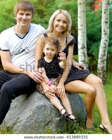 Beautiful woman with her husband and young daughter in green garden - stock photo