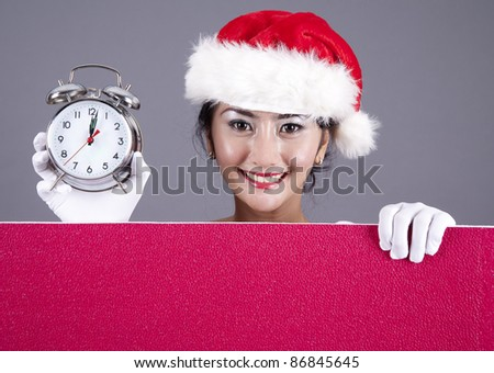 Beautiful woman with holding an alarm clock and a red blank sign - stock photo