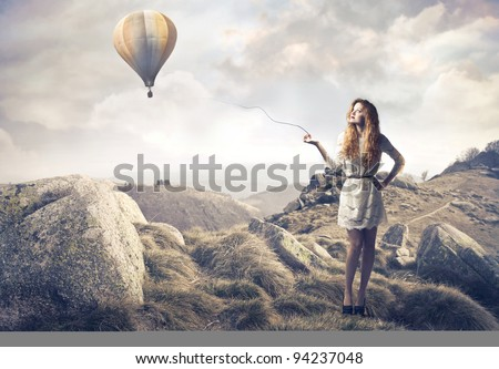 Beautiful woman with hot-air balloon in the background - stock photo