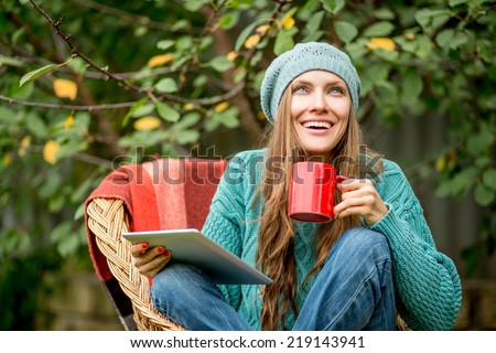 Beautiful woman with hot tea using tablet computer in autumn garden looking up. copy space - stock photo