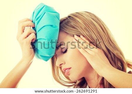 Beautiful woman with ice bag, having headache. - stock photo