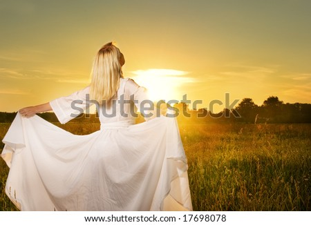 Beautiful woman with in the field at sunset - stock photo
