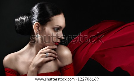 Beautiful woman with jewellery and red color scarf - stock photo