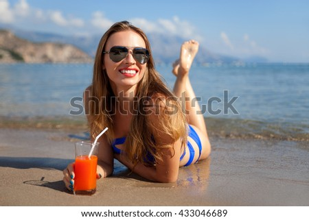 Beautiful woman with juice lying on a sand beach - stock photo