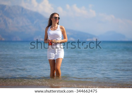 Beautiful woman with juice standing on a sand beach