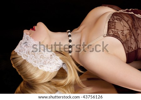 Beautiful woman with lace mask ?n a black background - stock photo