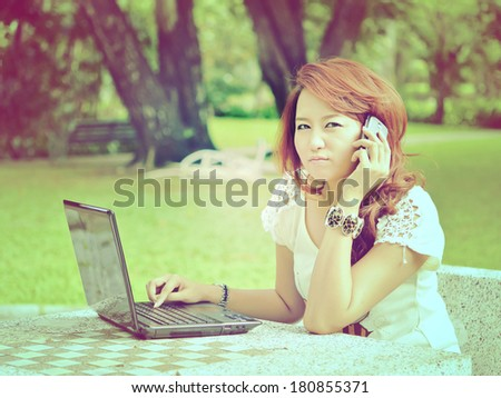 Beautiful woman with laptop and phone, vintage tone - stock photo