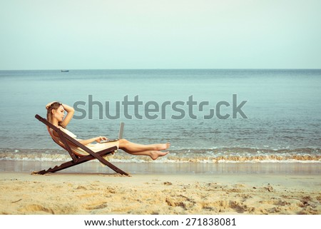 Beautiful woman with laptop on the sea