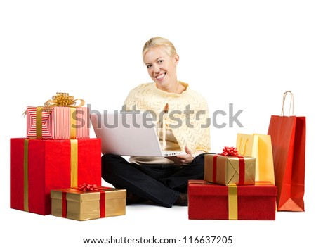 Beautiful woman with laptop surrounded by Christmas presents - stock photo