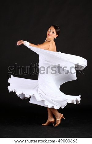 Beautiful woman with light skin wearing a long flowing gown and jewelry dancing against a black background - stock photo