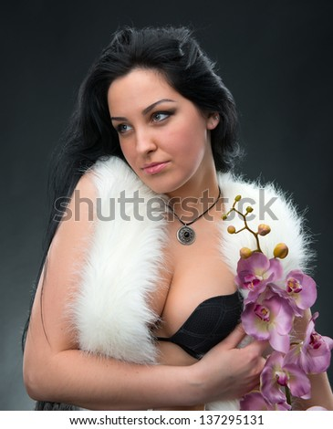 Beautiful woman with lilac orchid on a gray background