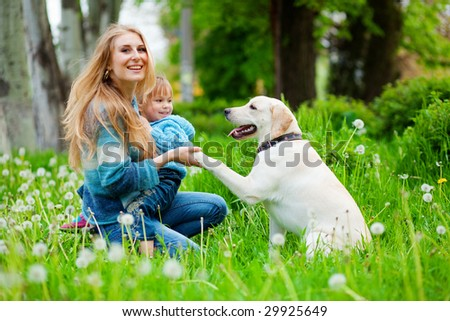 Beautiful woman with little girl and dog outdoors - stock photo
