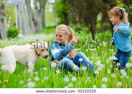 Beautiful woman with little girl and dog playing outdoors - stock photo