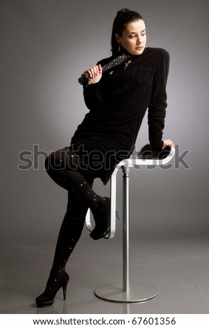 Beautiful woman with long blach hair and in black chlotes sitting on bar stool on gray background - stock photo