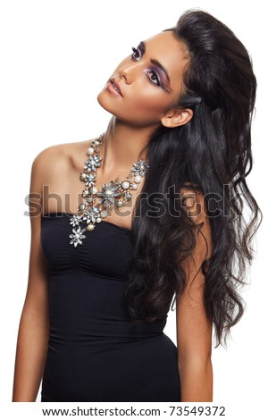 beautiful woman with long black curly hair, tanned skin and dramatic make-up wearing black dress and a flower expensive necklace over white background - stock photo