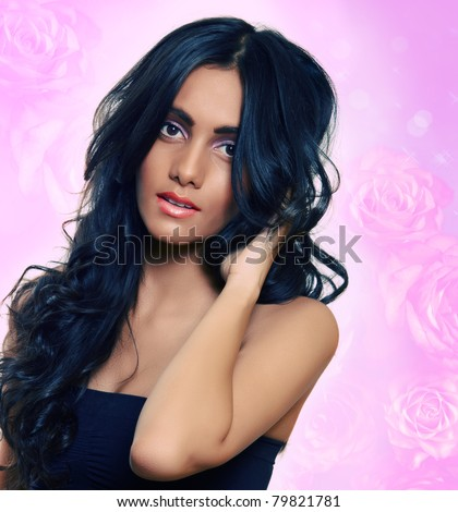 beautiful woman with long black curly hair, tanned skin and natural make-up over pink roses background - stock photo