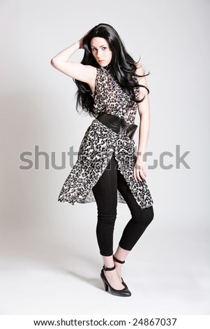 Beautiful woman with long black hair and fashionable outfit - stock photo