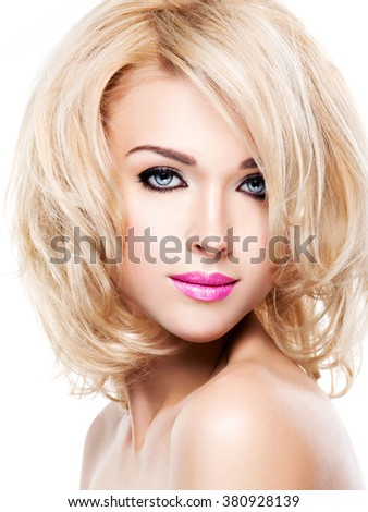 Beautiful woman with long blond curly hair. Portrait of fashion model with bright makeup. Isolated on white - stock photo