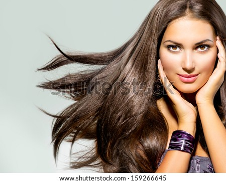 Beautiful Woman with Long Brown Hair. Blowing Hair. Closeup portrait of a Fashion Model Girl. Studio Shot - stock photo