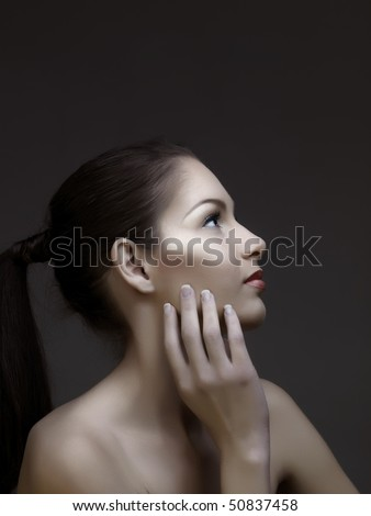 beautiful woman with long brown hair in a ponytail, touching her face - stock photo