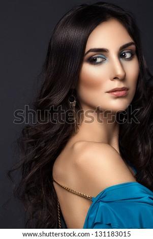 Beautiful woman with long brown hair posing at studio - stock photo
