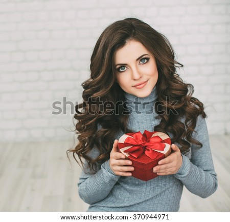 Beautiful woman with long curly hair holding gift box heart and looking at the camera. Valentine's Day. - stock photo