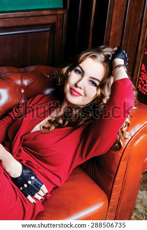 beautiful woman with long curly hair lying on the sofa in a luxury interior - stock photo