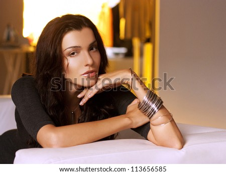 Beautiful woman with long dark hair looking into the camera - stock photo