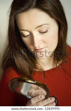 Beautiful woman with long dark hair wearing red blouse - stock photo