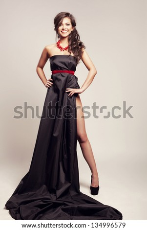 Beautiful woman with long evening black dress. Indoor
