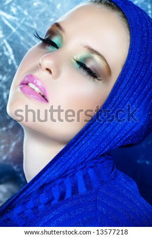 beautiful woman with long feather eyelashes in blue shiny metallic top with dreamy expression - stock photo