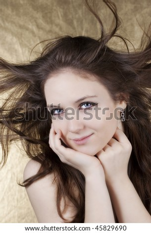 Beautiful woman with long hair in motion created by wind over white background