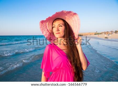 Beautiful woman with long hair on background of beach. Persian Gulf ,Dubai.Tanning girl near ocean, tropical resort, summer holiday - stock photo