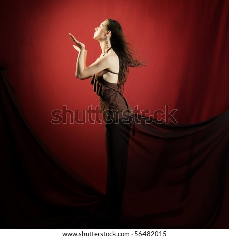 Beautiful woman with long hair posing on red backgrounds - stock photo