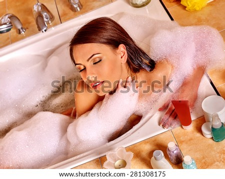 Beautiful woman with long hair relaxing at water in bubble bath. - stock photo