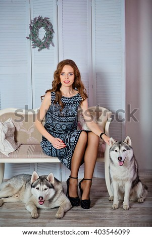 beautiful woman with long hair sitting on the sofa , on the floor beside her two Husky dogs sitting - stock photo