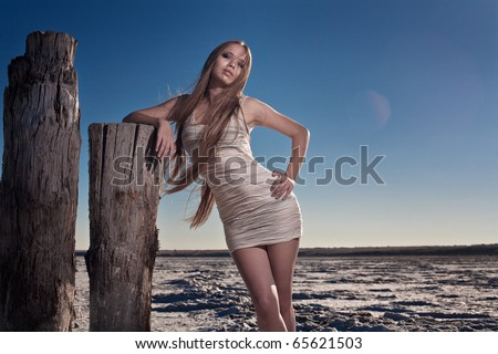 Beautiful woman with long hair standing outdoors - stock photo