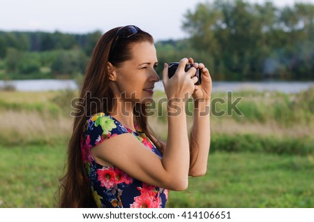 Beautiful woman with long hair taking pictures of the sunset on a summer evening - stock photo
