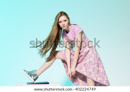 Beautiful woman with long legs in rose dress, chair and sneakers posing in the studio - stock photo