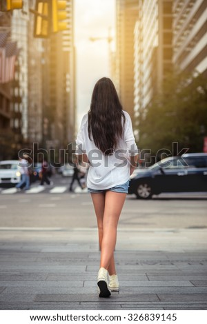 Beautiful woman with long legs walking around New York City street wearing jeans shorts. Rear view. - stock photo