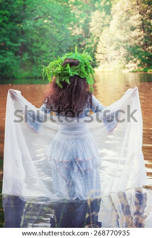 Beautiful woman with long medieval dress standing in the river outdoor - stock photo