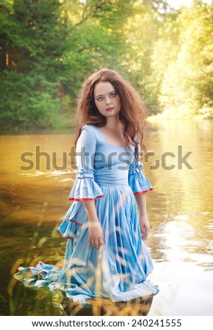 Beautiful woman with long medieval dress standing in the water  - stock photo