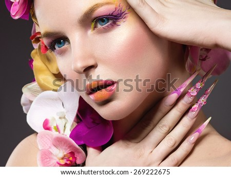 Beautiful woman with long nails, perfect skin, hair of orchids. Portrait shot in the studio. - stock photo