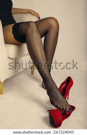 Beautiful woman with long sexy legs in the fishnet stockings. - stock photo