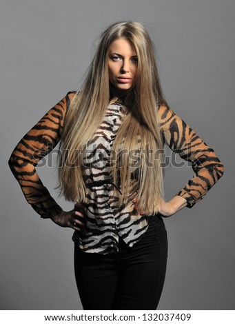 Beautiful woman with long straight blond hair. Fashion model posing at studio - stock photo